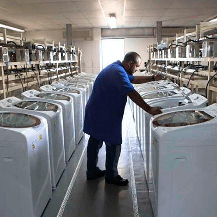 Homem em um corredor de máquinas de lavar apoiado em uma das máquinas.